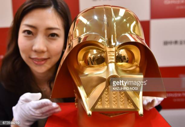 An employee of Japan's jeweler Tanaka Kikinzoku Jewelry displays a pure gold life size mask of Darth Vader a character in the Star Wars at their main...