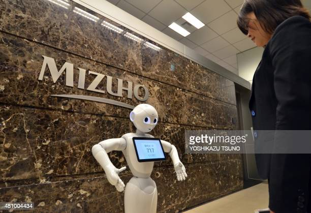 An employee of Japan's Mizuho Bank provides a demonstration on how to operate Softbank's humanoid robot Pepper at the bank's headquarters in Tokyo on...