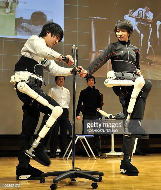 An employee of Japan's robot suit venture Cyberdyne demonstrates the new masterslave type HAL robotic exoskeleton which synchronizes the master's...