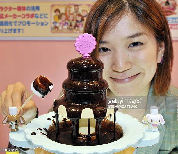An employee of Japan's toy giant Tomy displays a new cooking toy to make chocolate fondu called the 'Chocolate fountain' at the annual Tokyo toy show...