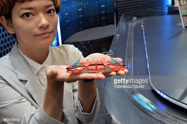 An employee of Japan's toy maker Tomy displays a prototype model of a maglev train 'Linear liner' at the Tokyo Toy Show in Tokyo on June 12 2014 Some...