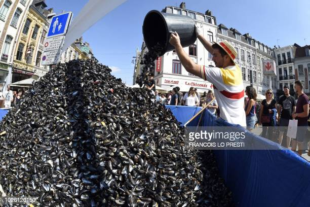 An employee of La Chicoree restaurant empties a bucket of empty mussel shells onto a pile during the annual Braderie de Lille on September 2 in Lille...