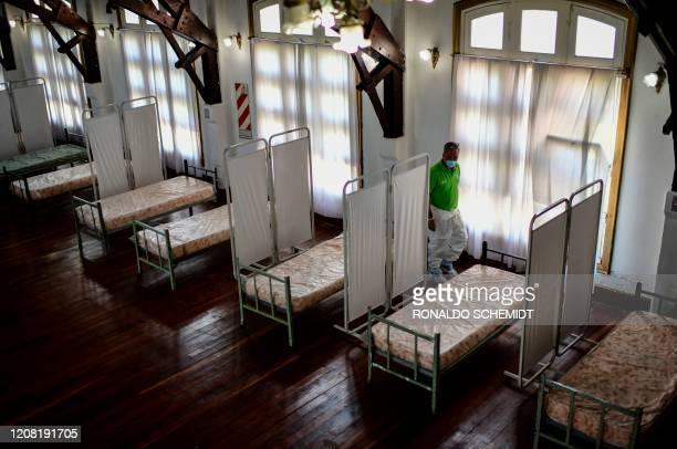 An employee of La Plata municipality arranges beds for COVID-19 coronavirus patients inside the Republica de los Ninos amusement park in La Plata, on...