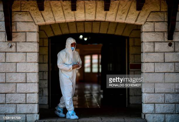 An employee of La Plata municipality wearing a protective suit leaves a room where COVID-19 coronavirus patients will be isolated at the Republica de...