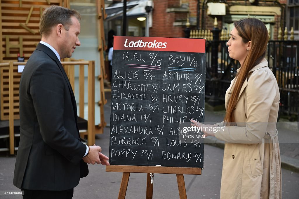 An employee of Ladbrokes betting company (R) is interviewed by a member of the media as she stands by a blackboard with the odds of the sex and name of the upcoming royal baby outside the Lindo Wing of St Mary's hospital in central London where Catherine, Duchess of Cambridge is expected to give birth to her second child. Punters think the baby will be a girl, with Alice the clear favourite for the name. NEAL