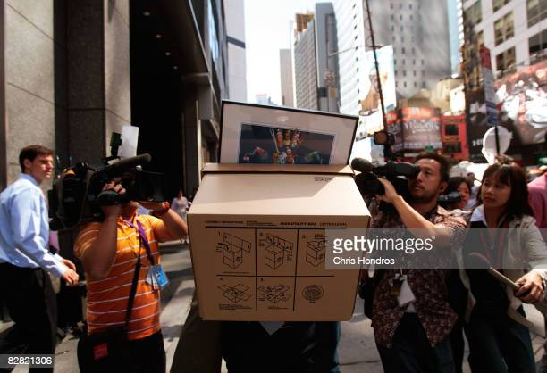 An employee of Lehman Brothers Holdings Inc carries a box out of the company's headquarters as he is followed by the media September 15 2008 in New...