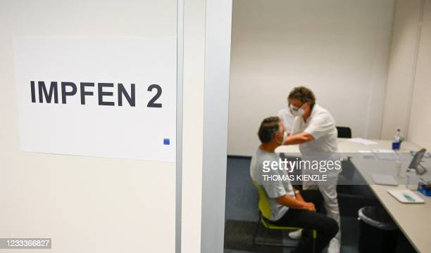 An employee of machine tools and laser technology company Trumpf is vaccinated with the BioNTech/Pfizer vaccine at the company's vaccination center...