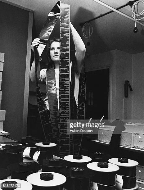 An employee of Mansell Information/ Publishing checks a 200 foot roll of film produced by the special camera which is used to photograph library...