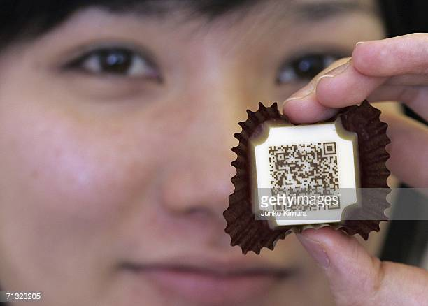 An employee of Mary Chocolate Co displays a piece of chocolate decorated with a URL written in twodimensional code on June 29 2006 in Tokyo Japan The...