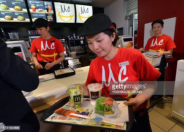 An employee of McDonald's Japan serves the new menu 'Vegetable Chicken Burger' as the company president Sarah Casanova announces the new business...