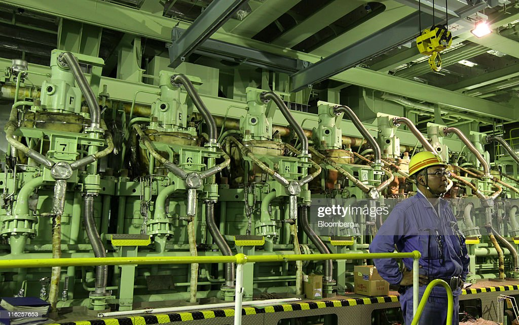 An employee of Mitsubishi Heavy Industries Ltd. stands in the engine room of the Nippon Yusen K.K.'s car transporter ship, Auriga Leader, at the Honmoku plant in Yokohama city, Kanagawa prefecture, Japan, on Wednesday, June 15, 2011. Nippon Yusen K.K. is Japan's largest shipping line. Photographer: Tomohiro Ohsumi/Bloomberg via Getty Images