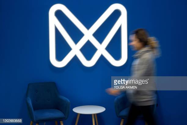 An employee of mobile phone appbased 'neobank' Monese walks past the company's logo at its offices in London on February 7 2020 Among Britain's...