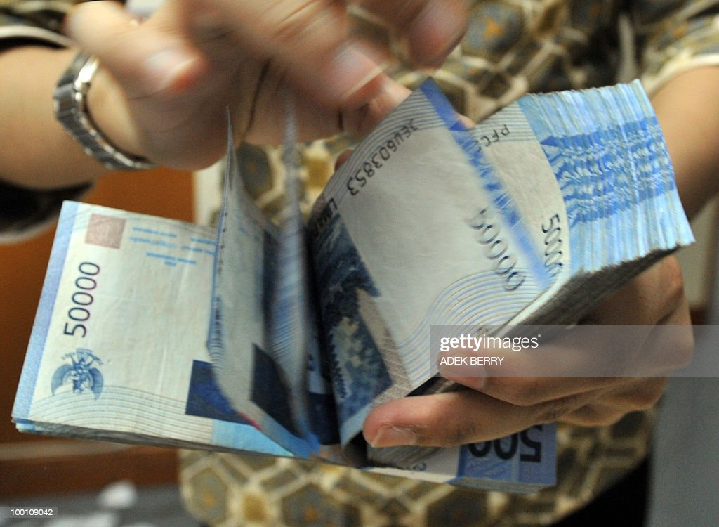 An employee of money changer counts Rupiah notes in Jakarta on May 21, 2010.