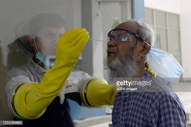 An employee of Mugda Medical College and Hospital collects a swab sample from a resident to be tested. Mugda Medical College and Hospital employees...