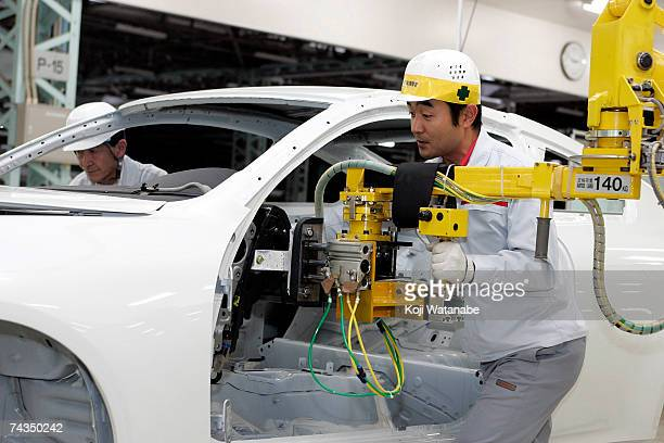 An employee of Nissan Motor Company works on the assembly line at Nissan's Global Production Engineering Center on May 29 2007 in Zama Japan The GPEC...