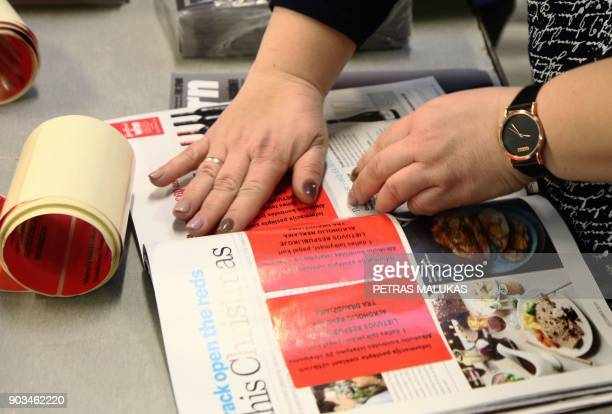 An employee of Press Express the largest distributor of foreign papers plasters over alcohol ads with blanket ban on alcohol ads on pages of a...