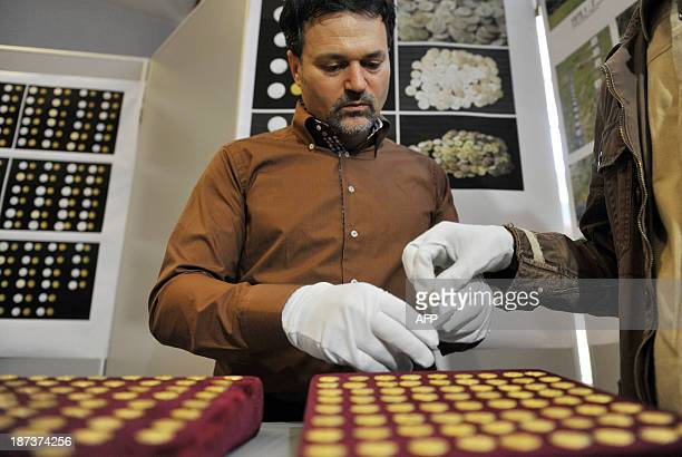 An employee of Romanian National History museum shows golden coins in Bucharest on November 8 2013 part of an unveiled collection of ancient gold...