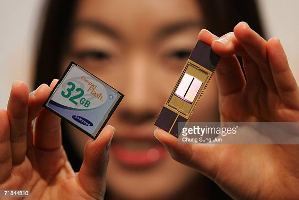 An employee of Samsung Electronics Co Ltd shows new 32Gigabyte NAND memory chip and card during the news conference at the Shilla hotel on September...