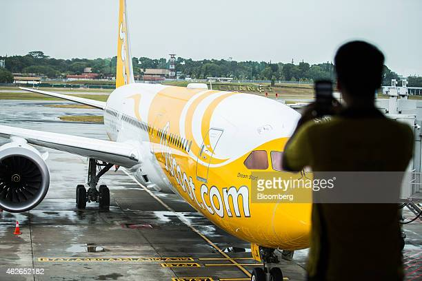 An employee of Scoot Pte a unit of Singapore Airlines Ltd takes a photograph of a Boeing Co 787 Dreamliner aircraft as it sits on the tarmac at...