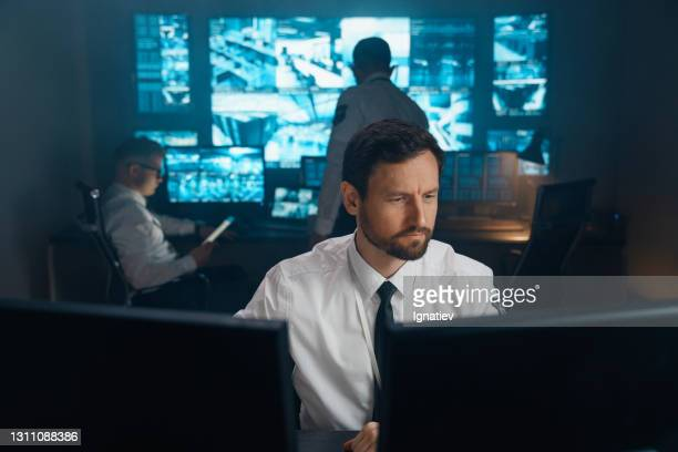 an employee of security, security, police, rescue service, fbi, cia, sits at his workplace behind monitors. - police force stock pictures, royalty-free photos & images