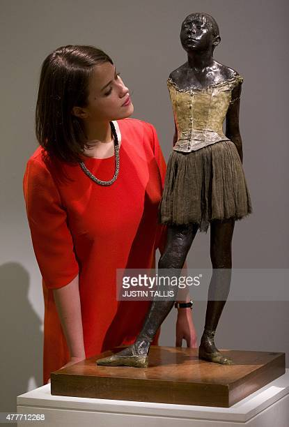 An employee of Sotheby's auction house poses by Petite danseuse de quatorze ans by French artist Edgar Degas executed in wax circa 187981 and cast in...
