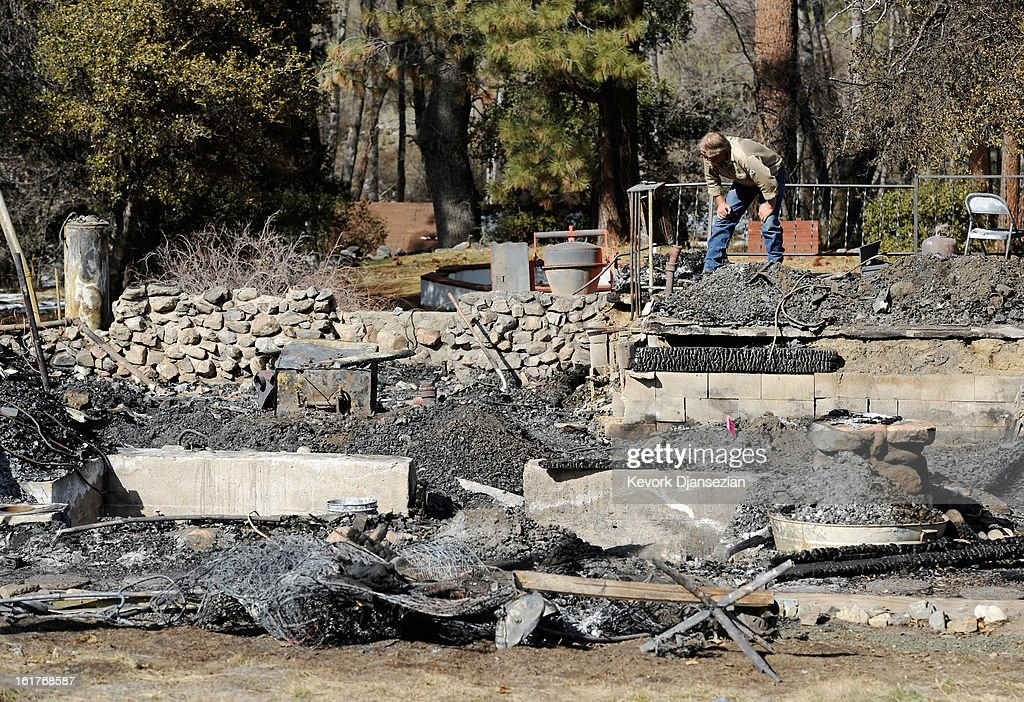 An employee of Southern California Edison surveys the damage at the burned-out cabin where the remains of multiple murder suspect and former Los Angeles Police Department officer Christopher Dorner were found on February 15, 2013 in Big Bear, California. Dorner, a Navy Reserve veteran, barricaded himself in the cabin and engaged law enforcement officers in a shootout, killing one and wounding another. Dorner's body was identified after being found in the burned out cabin.