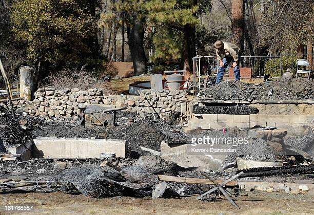 An employee of Southern California Edison surveys the damage at the burnedout cabin where the remains of multiple murder suspect and former Los...