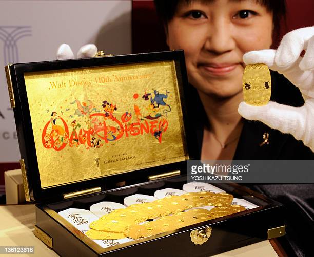 An employee of Tanaka Kikinzoku Jewelry displays a pure gold made oval coin designed with Mickey Mouse and Walt Disney on its surface for the...