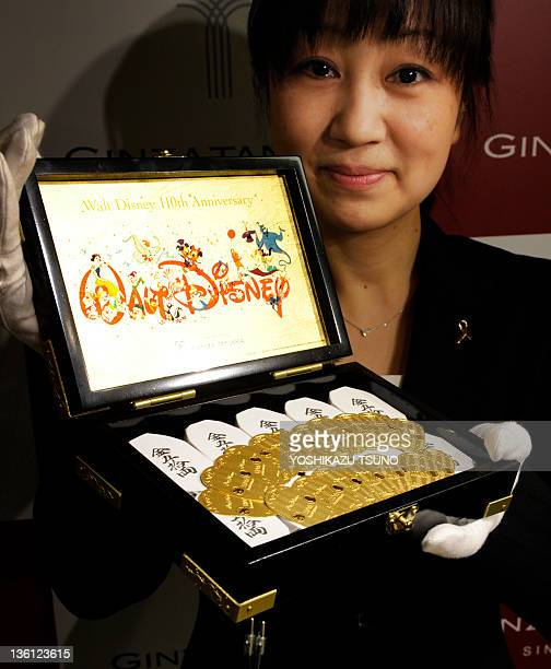An employee of Tanaka Kikinzoku Jewelry displays pure gold oval coins designed with Mickey Mouse and Walt Disney on its surface for the celebration...