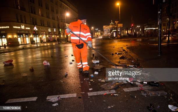 An employee of the Berlin City Cleaning Services clears remaining garbage of the New Year's Eve party in front of the Brandenburg Gate, a major...