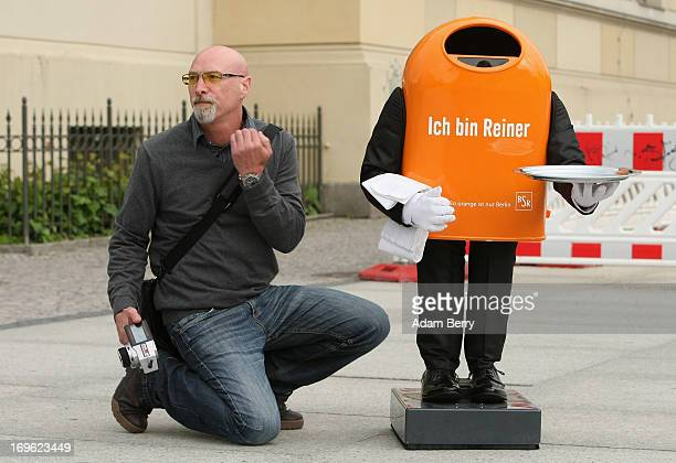 An employee of the Berliner Stadtreinigungsbetriebe city garbage removal company holding a remote control in his hand signals to a colleague that the...