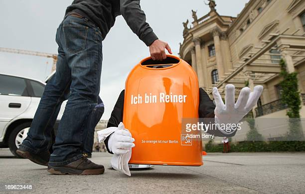 An employee of the Berliner Stadtreinigungsbetriebe city garbage removal company lifts the top half of a broken trash canshaped robotic butler named...