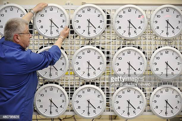An employee of the Bodet Company adjusts a clock on March 26 2014 at the plant of Trementines western France The Bodet company manufactures clocks...