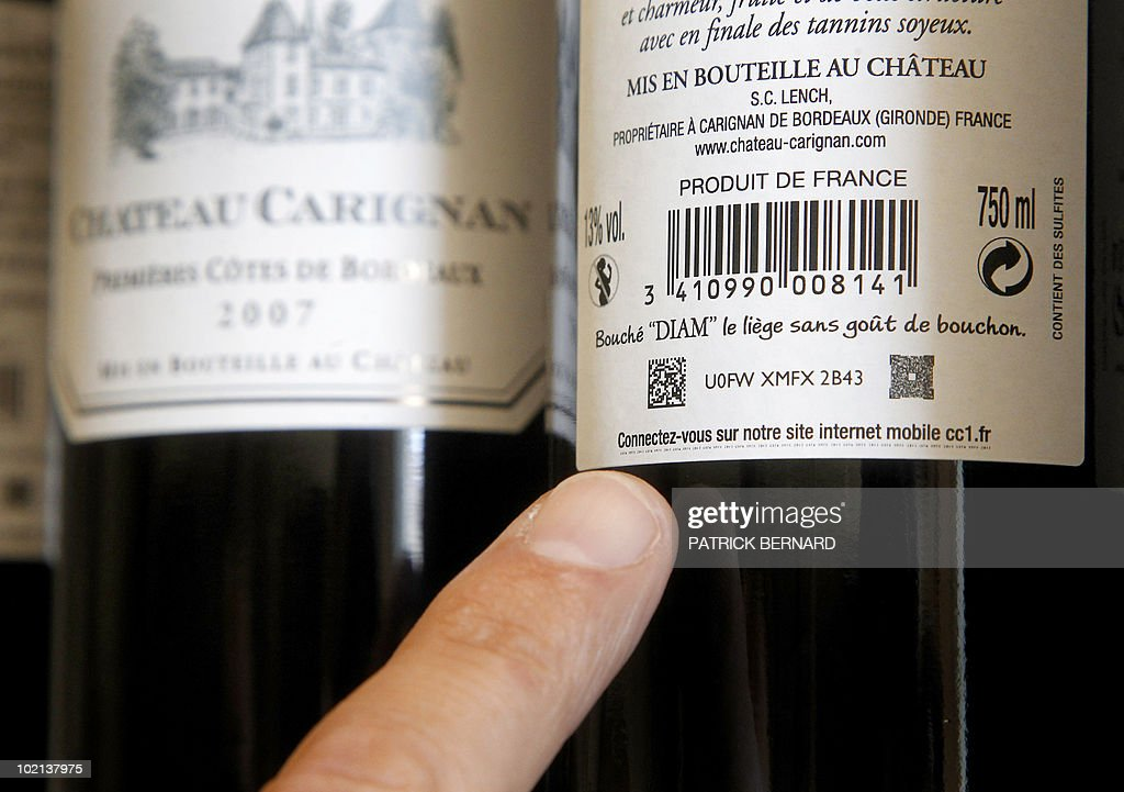'UN TATOUAGE NUMERIQUE POUR SUIVRE A LA TRACE SA BOUTEILLE DE BORDEAUX' - An employee of the Chateau Carignan wine indicates a numeric marker included in a bottle label permitting the tracking of the wine bottle with any smart phone, on June 6, 2010 in Carignan-de-Bordeaux, western France. From now on, consumers can know the distance covered by a Bordeaux's bottle from a picture of the label. This tracking system was generalized to all Bordeaux wines.