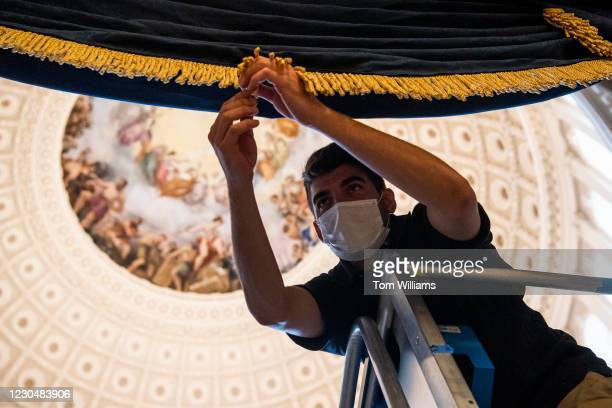 An employee of the Chief Administrative Office hangs drapes in the Capitol Rotunda for the upcoming presidential inauguration on Friday, January 8,...