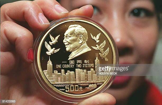 An employee of the China Gold Coin Corporation displays a 9999% pure gold coin newly issued by the People's Bank of China to commemorate the return...