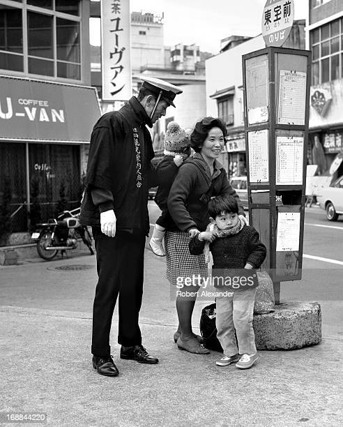 An employee of the city's tourism and information office offers assistance to a women with two children waiting for a bus in the hot springs resort...
