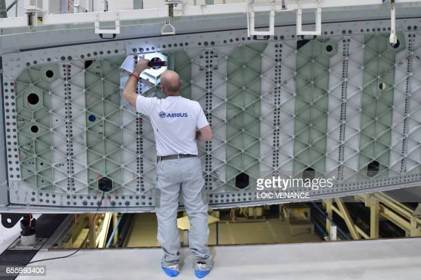 An employee of the civil aircraft manufacturing company Airbus works on March 20 2017 at the Airbus facility in Bouguenais western France / AFP PHOTO...