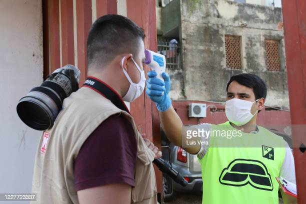 An employee of the Club measures the temperature to a photographer as part of preventive measures before a match between River Plate and Nacional as...