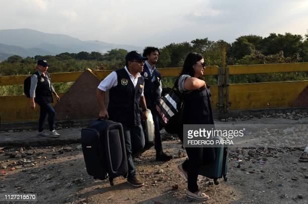 An employee of the Colombian Consulate in Valencia Venezuela walks followed by the Colombian Consul in Merida Venezuela Carlos Garcia as they cross...