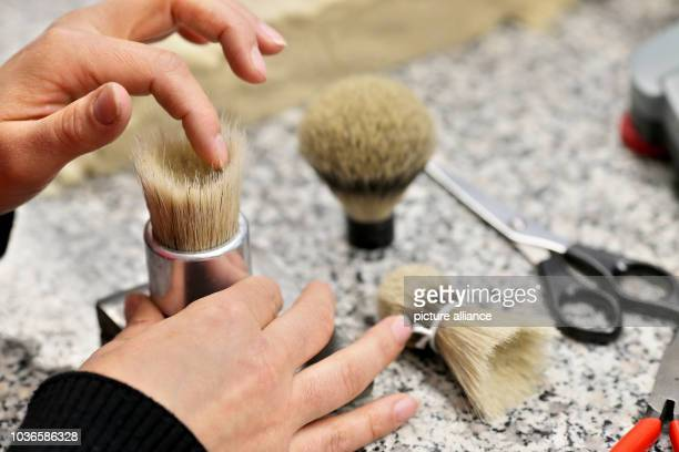 An employee of the company HansJuergen Mueller GmbH moulds a bundle of badger hair for a shaving brush in Stuetzengruen Germany 24 May 2016 The...