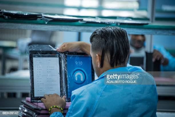 An employee of the Cuban state Informatics Communications and Electronics Industrial Enterprise assembles tablets and laptops with technology of the...