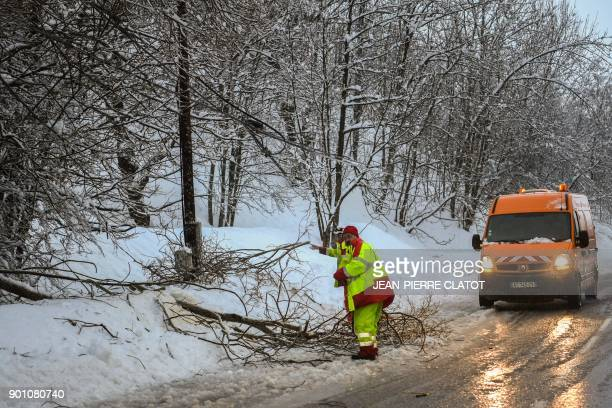 An employee of the Departmental Infrastructure Authority clears fallen tree branches from a road leading to the French Alps ski resorts of Les...