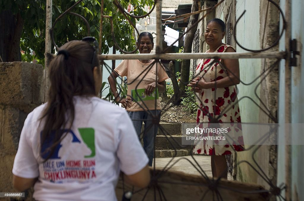 An employee of the Dominican Ministry of Public Health speaks with two locals during an information campaign to prevent the spread of the mosquito which transmits the Chikungunya virus, in the district of 'La Agustinita', in Santo Domingo, on May 30, 2014.