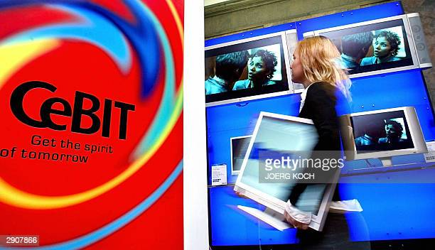 An employee of the elctronic company Iiyama ProLite carries a E481S IT-LCD screen during a press preview of the CeBit fair in Munich 28 January 2004....