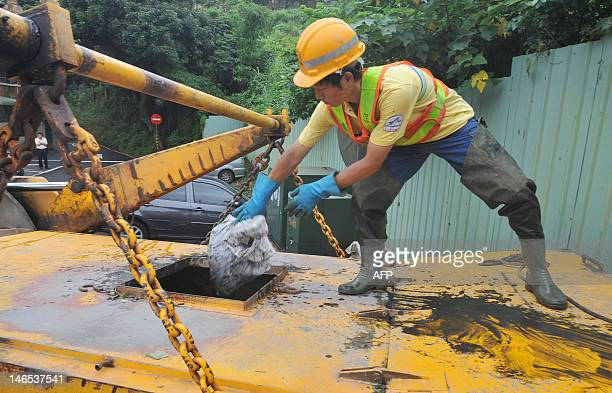 An employee of the environmental protection agency cleans up a road in Wenshan District of Taipei on June 19 2012 Taiwan's Central Weather Bureau...