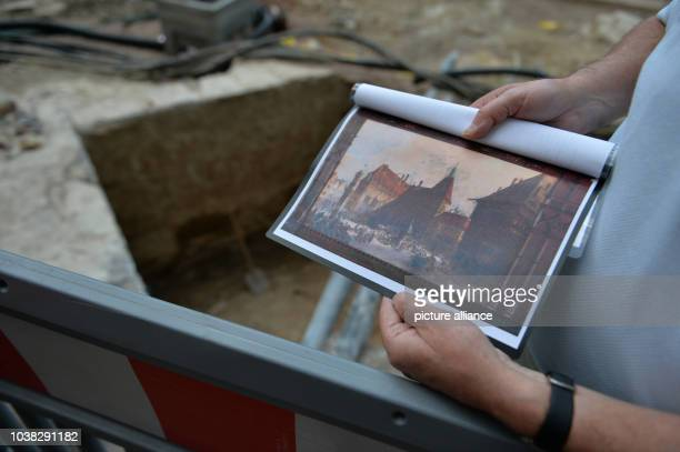 An employee of the Erfurt Tiefbauamt holds a picture of the city hall in front of the remains of the historical city hall tower from 1330 in Erfurt...