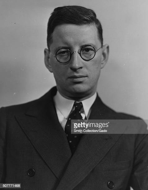 An employee of the Farm Security Administration wearing a suit and glasses poses for a portrait 1935 From the New York Public Library