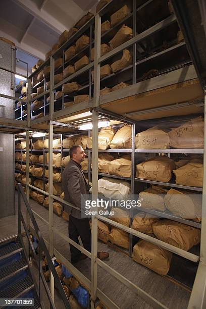 An employee of the federal archive responsible for the files of the former East German secret police the Stasi guides a journalist among sacks...