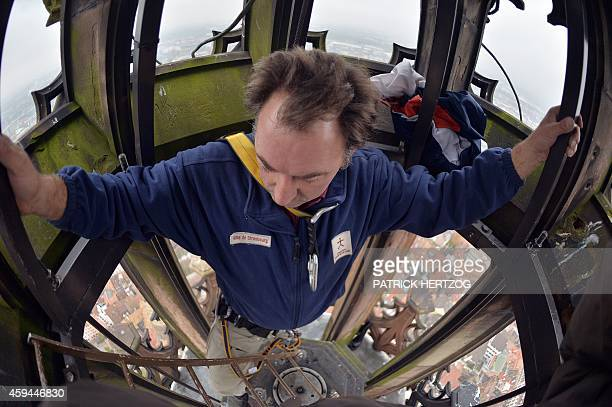 An employee of the Fondation de l'uvre NotreDame climbs on the top of the spire of the Strasbourg Cathedral to raise the French flag during a...